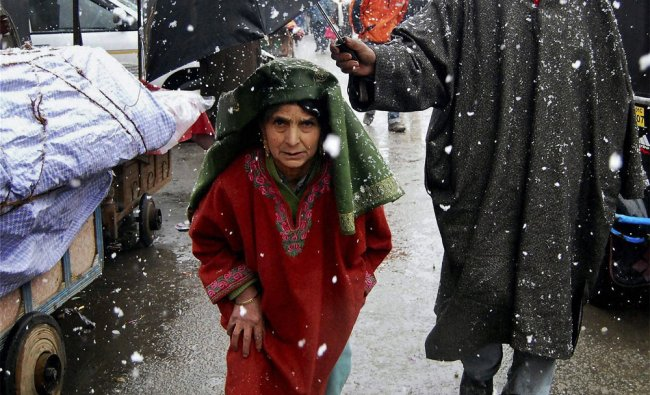 A man covers an old woman with an umbrella as it snows in Srinagar