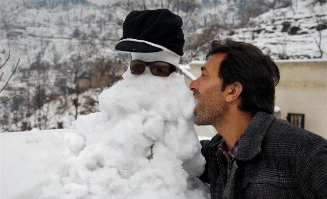 A man kisses an artificial snow man