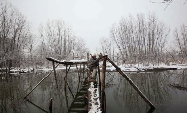 Kashmiri man makes his way through a foot bridge after a fresh snowfall