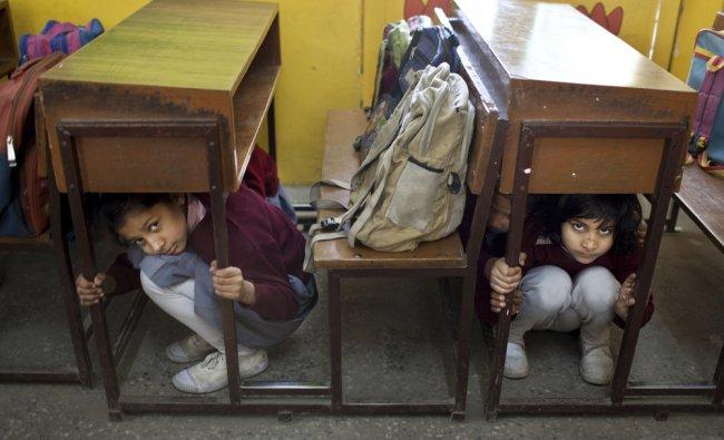 Schoolgirls lie low under their desks during a disaster drill