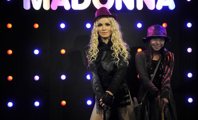 A tourist strikes a pose next to a wax figure of US singer Madonna
