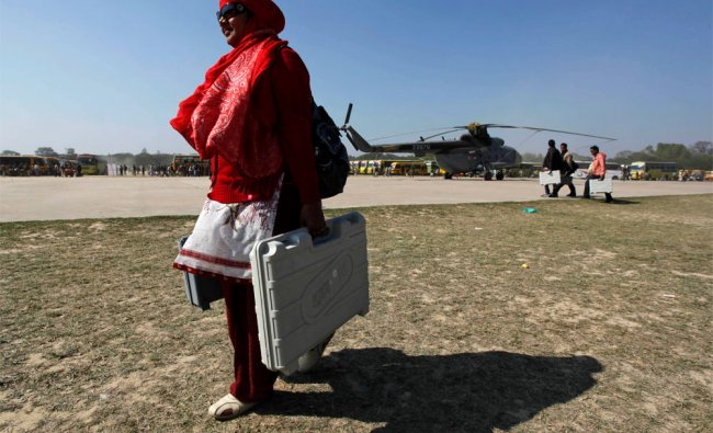 A polling official carrying electronic voting machines heads towards her assigned polling station