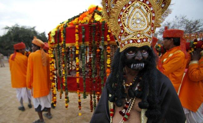 A devotee dressed as a demon participates in a procession ahead of Shivratri festival