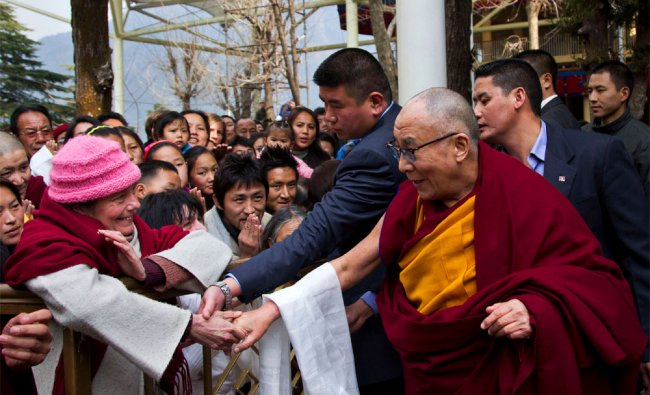 Dalai Lama greets a devotee as he leaves after leading a prayer session