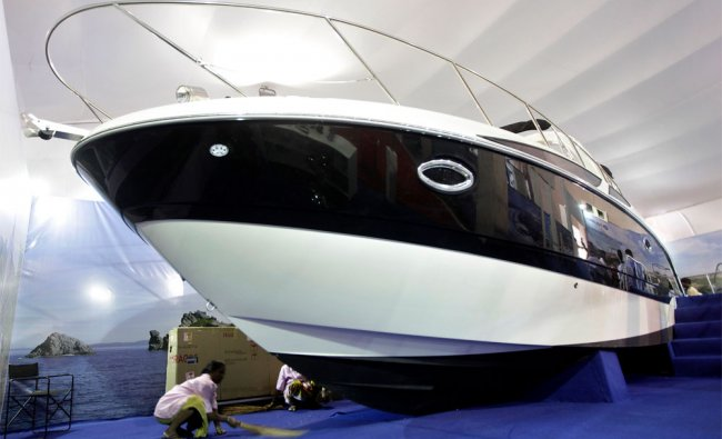 A worker sweeps the floor under a boat displayed at the Mumbai International Boat Show