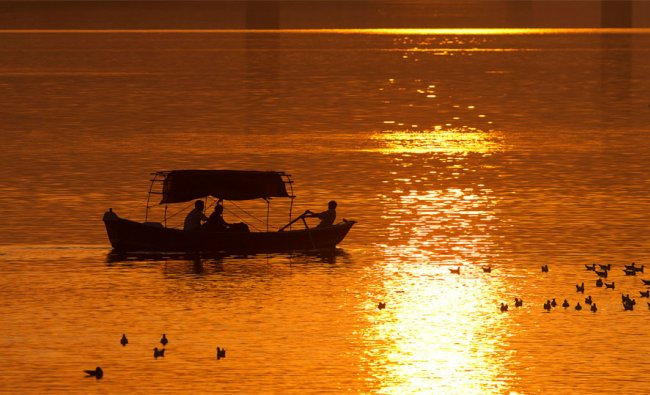 Tourists take a boat ride on the River Ganges at sunset in Allahabad