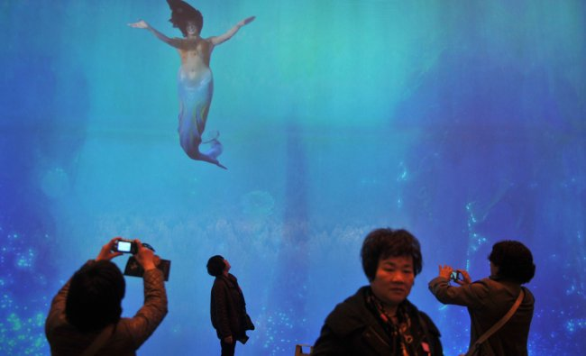 Mainland Chinese tourists take pictures of a large display showing mermaids...