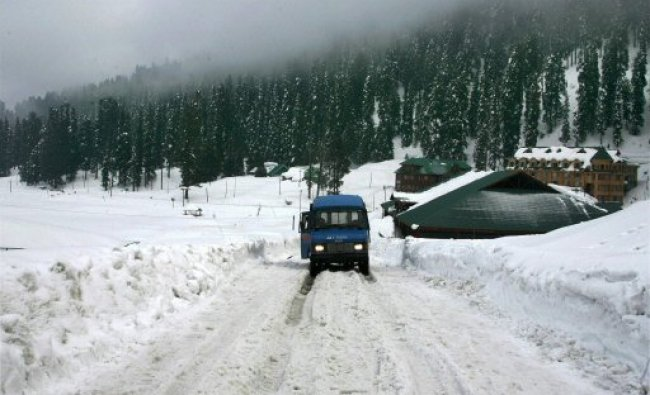 A vehicle moving slowly at a snow covered road at the...