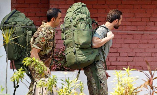 Italian marines accused of killing two Indian fishermen walk towards a police vehicle
