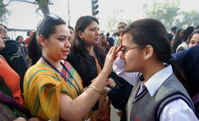 Teachers wishing good luck to students at an examination centre