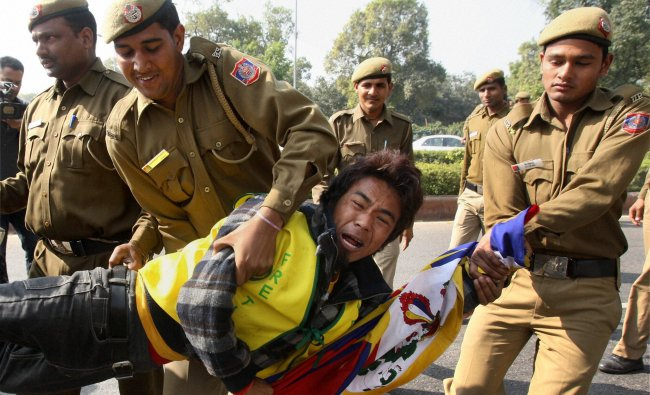 Police detain one of the Tibetan exiles during a protest...