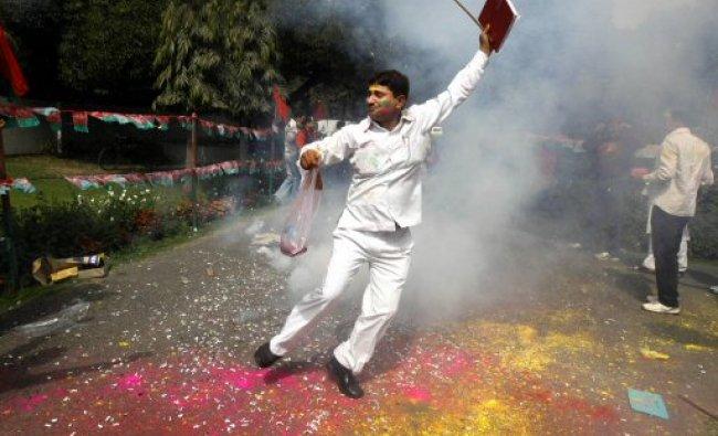 A Samajwadi Party supporter throw dances amid smoke...