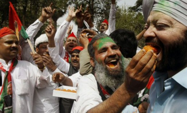 Samajwadi Party supporters exchange sweets...