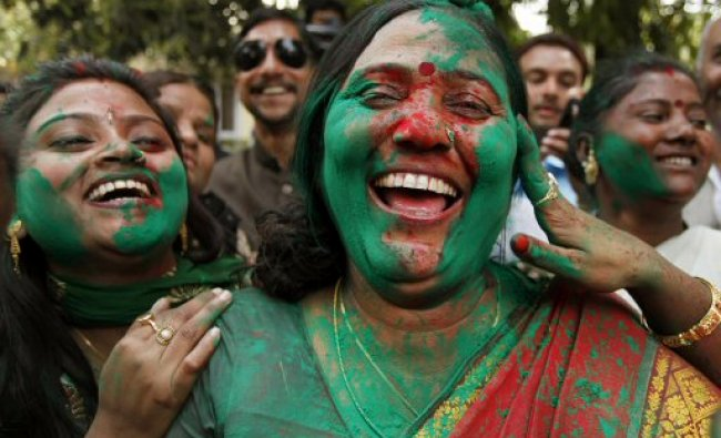 Samajwadi Party supporters smear each others\' faces with colored powder as they celebrate...