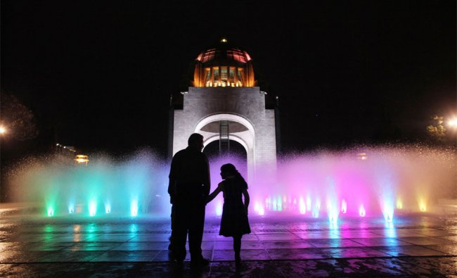 People enjoy a fountain in front of the Revolution Monument in Mexico City