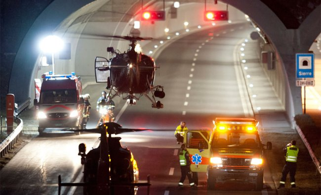 Swiss rescue workers stand in front of the tunnel entrance after a bus crashed in the tunnel
