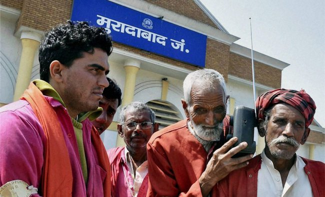 Porters listening to the Railway budget 2012-13 speech on a radio set in Moradabad