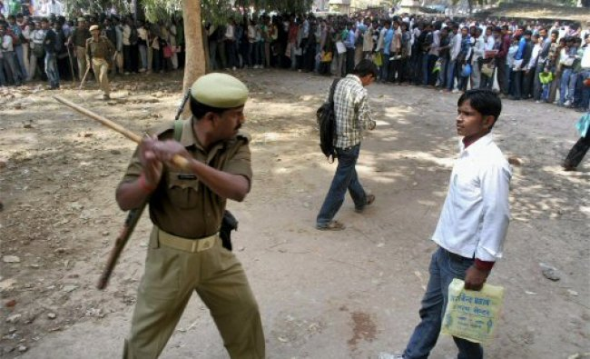 A policeman charges a youngster as unemployed youth...