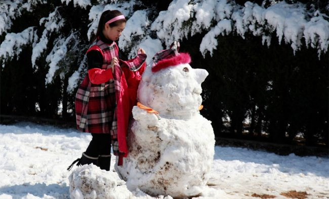 A Chinese girl dresses up a snow man in Beijing