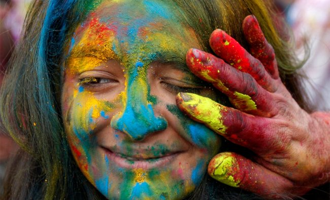 A woman gets her face smeared with colored powder during \'Holi\' in Malaysia