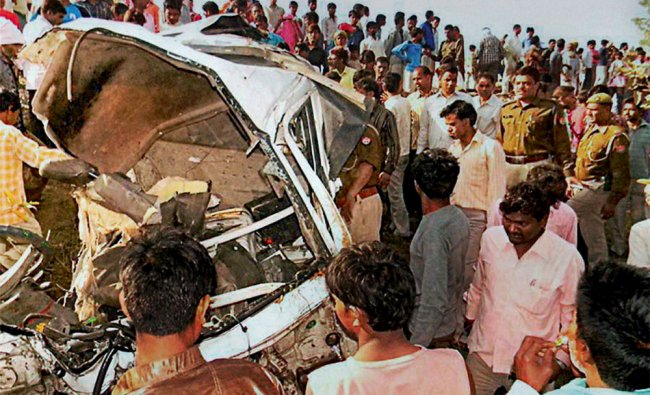Police and locals near the mangled vehicle which was hit by a passenger train in Hathras