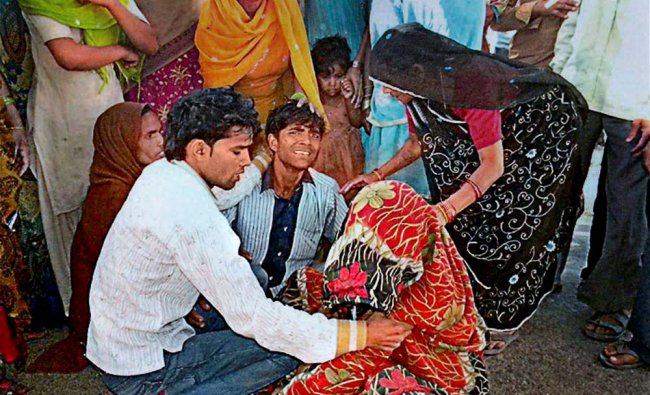 Crying relatives of the victims who died after a passenger train hit a jeep in Hathras