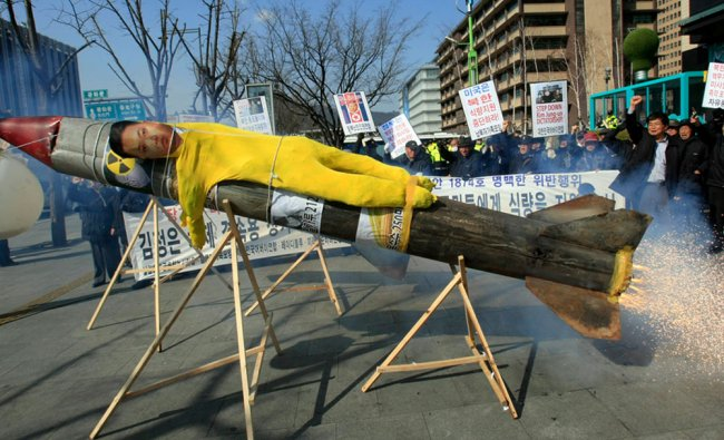 An effigy of North Korean leader Kim Jong Un is put on a mock North Korean missile during a rally