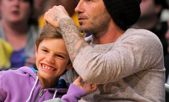 Soccer player David Beckham and his son Romeo watch a NBA basketball game