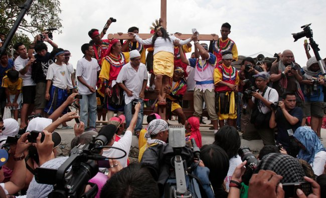 Filipino woman penitent Percy Valencia is nailed to a wooden cross during Good Friday rituals