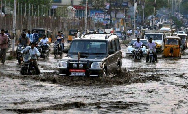 Vehicles wade through a waterlogged road...