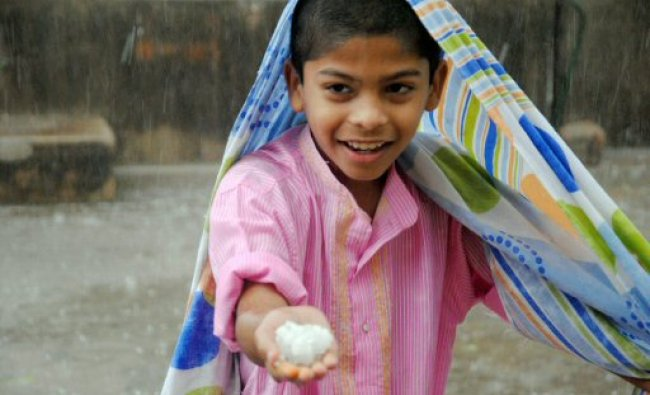 A boy shows hails during a hail-storm in Hyderabad...