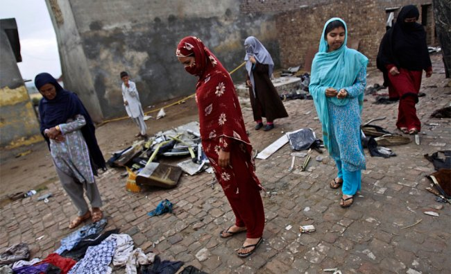 Pakistani women look at clothes and stuff belonging to passengers of a Bhoja Air Boeing 737