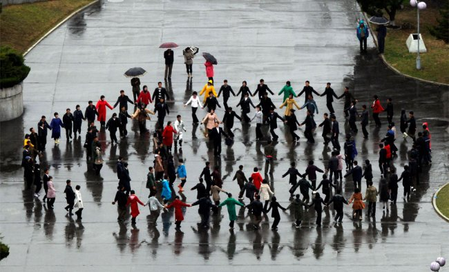 North Koreans gather to practice dance formations on a cold rainy day in Pyongyang