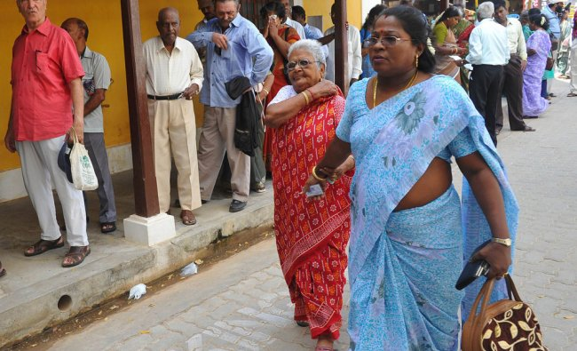 An elderly Indo-French citizen is escorted to a polling both by an assistant in Pondicherry