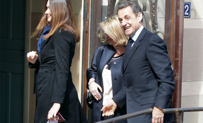 French President Nicolas Sarkozy arrives with his wife to cast his vote in first round of elections
