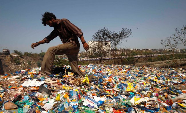 A rag picker walks over waste material discarded in a slum area in Mumbai on World Earth Day