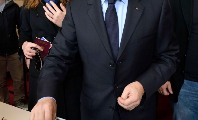 French President Nicolas Sarkozy is watched by his wife Carla Bruni-Sarkozy as he casts his vote