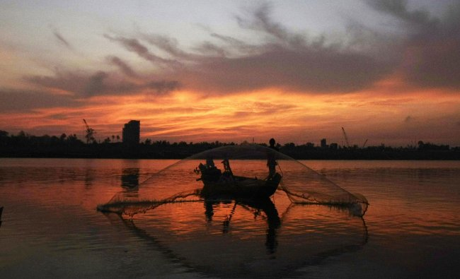 A Cambodian fisherman throws his fishing net in the morning
