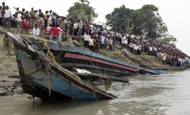 Rescuers pull out the wreckage of a ferry that capsized in the Brahmaputra River...