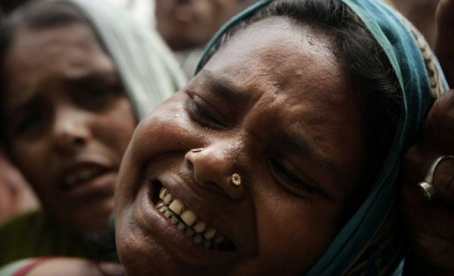 A relative cries near the dead body of a person who died after a ferry capsized...