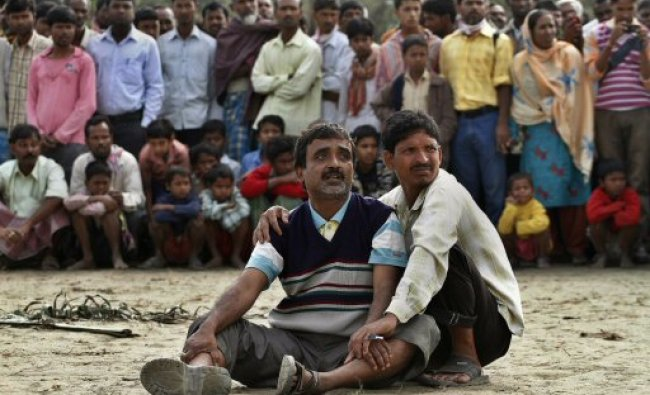 Abdul Mazid, 42, center, whose sister is missing anxiously watches rescuers pull out the wreckage..