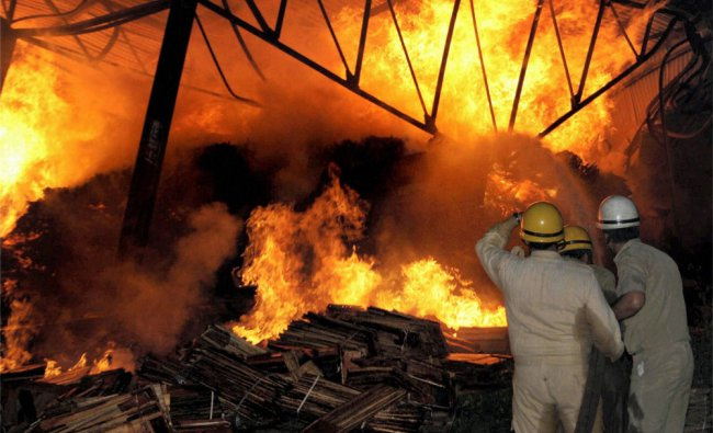 Firemen try to douse the flames after a major fire broke out in Narwal vegetable market in Jammu