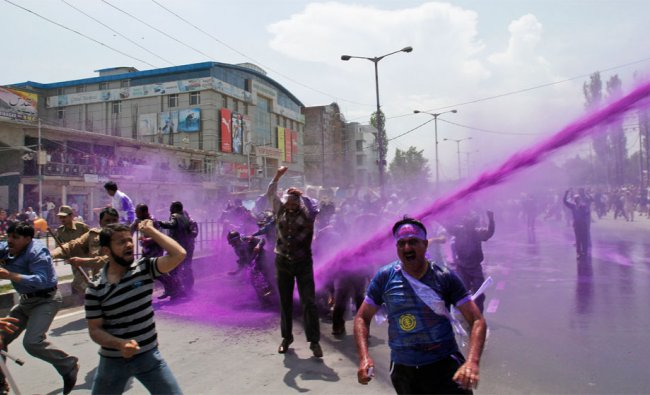 Police use colored water from a water cannon to disperse protesting Kashmiri government employees