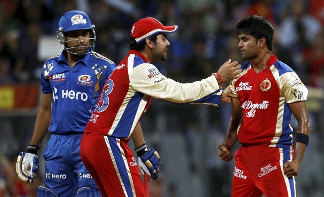 Royal Challengers Banglore\'s Virat Kohli, left and Vinay Kumar celebrate the wicket of Rohit...