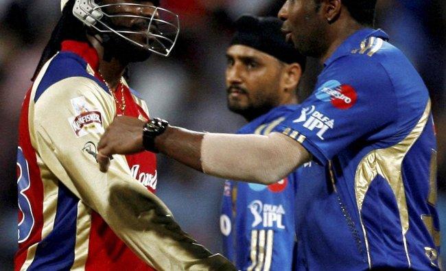Royal Challengers Bangalore batsman Chris Gayle being greeted by Mumbai Indians K Pollard and...