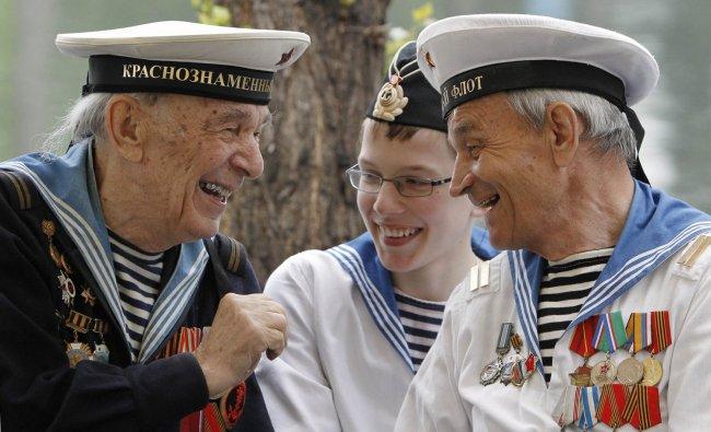 World War II veterans share a joke as a boy wearing a navy uniform listens to them, during a...