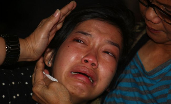 A relative weeps as she waits for the news on the missing Russian airplane