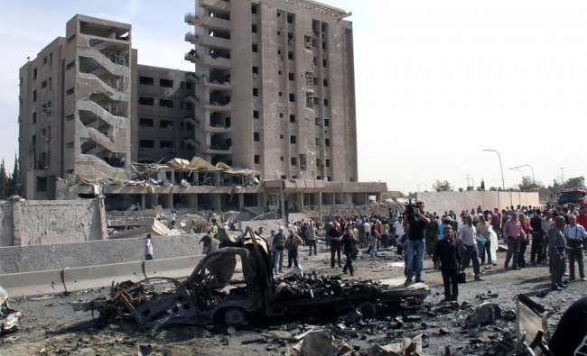 Syrian gather in front of a damaged military intelligence building after a bomb explosion