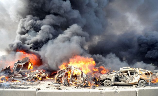Burning cars at the site of a bomb explosion in Syria
