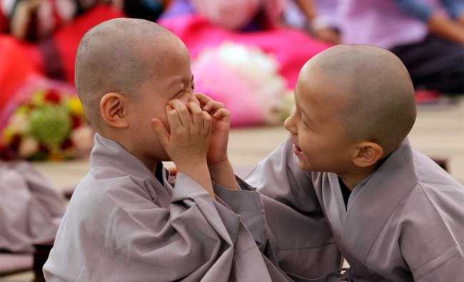 Shaven-headed young boys play during a service to celebrate Buddha\'s upcoming birthday